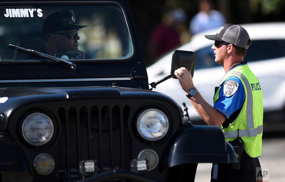 Wrightsville Beach Police Det. Greene checks identification at the bridge to Wrightsville Beach, N.C., Wednesday, Sept. 12, 2018. The island closed to non-residents at 8 a.m. The effects of Hurricane Florence in Southeastern North Carolina are expected to begin Thursday. (Matt Born/The Star-News via AP)