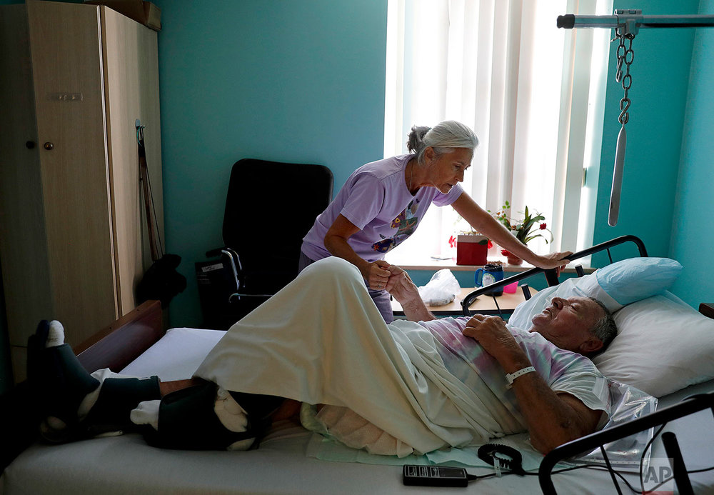 "Marge Brown, 65, says goodbye to her father, George Brown, 90, before he is evacuated from a healthcare home in Morehead City, N.C., Wednesday, Sept. 12, 2018, as Hurricane Florence approaches the east coast. ""I'd like to stay and see what happens. I'm 90 plus,"" said Brown, a WWII veteran who says he's survived a plane crash and severe burns from a laboratory fire where he once worked. (AP Photo/David Goldman)"