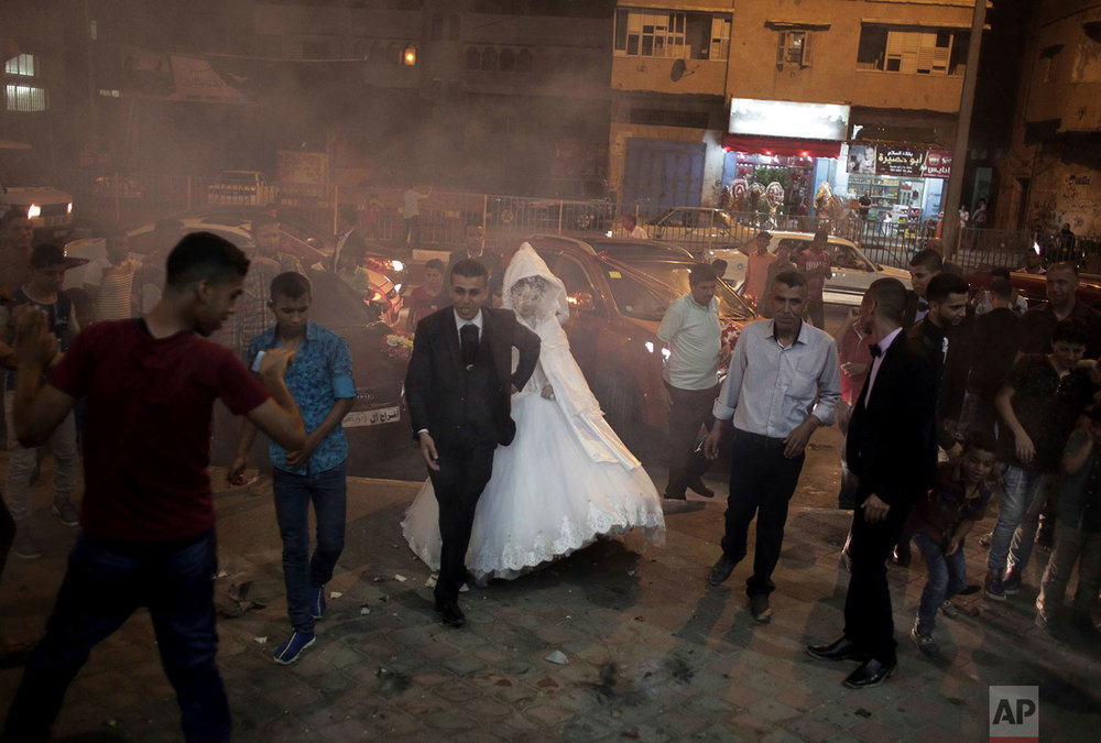 In this July 31, 2016 photo, Palestinian groom Saed Abu Aser, and his bride, Falasteen, walk into the wedding hall, in Gaza City. (AP Photo/Khalil Hamra)