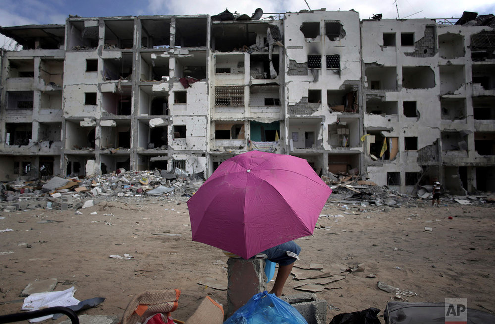 In this Aug. 11, 2014 photo, a Palestinian boy holds an umbrella as he rests in front of the damaged Nada Towers residential neighborhood in the town of Beit Lahiya, northern Gaza Strip. (AP Photo/Khalil Hamra)