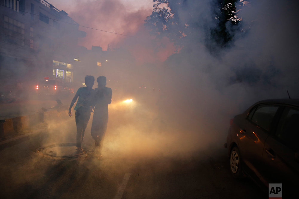 Boys walk past smoke from fumigation being carried out to prevent the spread of mosquito-borne diseases in Allahabad, India, Thursday, Sept. 13, 2018. More than 200 million people live in impoverished Uttar Pradesh, India's most populous state. Thousands of people suffer from encephalitis, malaria, typhoid and other mosquito-borne diseases each year during the summer monsoon. (AP Photo/Rajesh Kumar Singh)