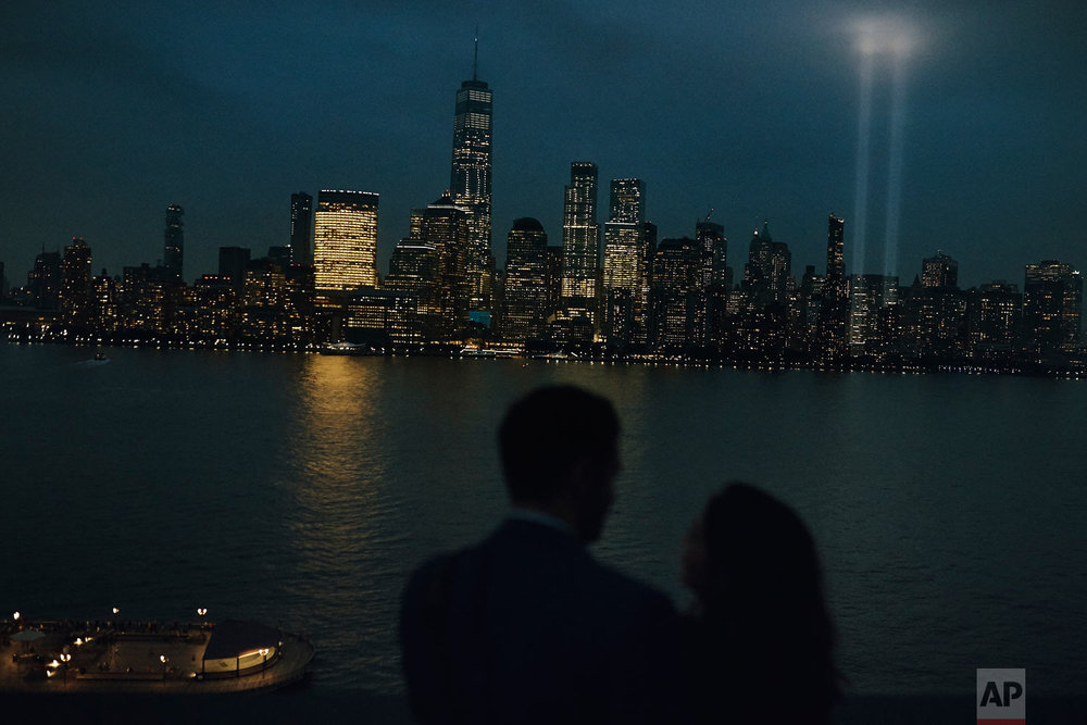 "A couple hugs across the Hudson River in Jersey City, N.J., as the ""Tribute in Light"" is projected in the sky above the lower Manhattan area of New York, on the 17th anniversary of the Sept. 11 terror attacks, Tuesday, Sept. 11, 2018. (AP Photo/Andres Kudacki)"