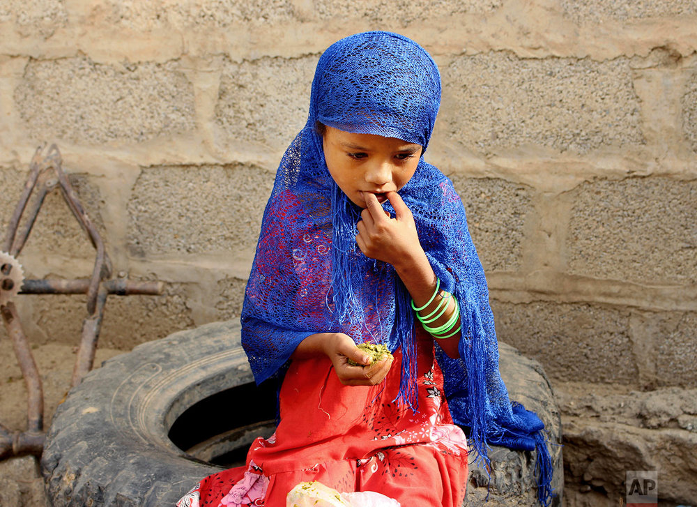 A girl eats boiled leaves from a local vine to stave off starvation, Aug. 25, 2018, in the extremely impoverished district of Aslam, Hajjah, Yemen. (AP Photo/Hammadi Issa)