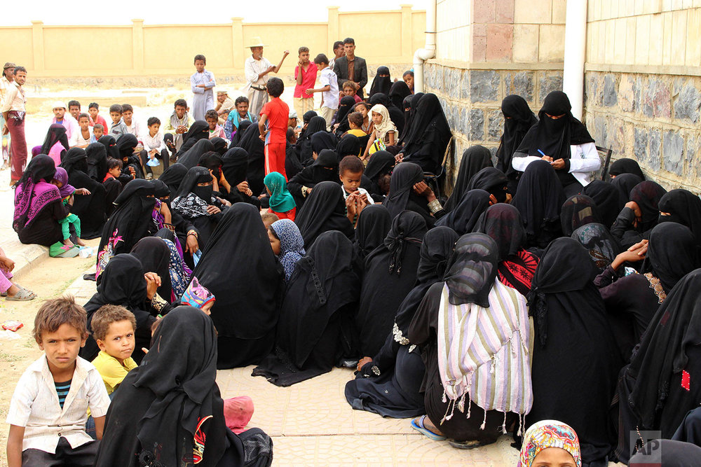 Women wait with their children in front of the Aslam Health Center, Aug. 25, 2018, in Hajjah, Yemen. (AP Photo/Hammadi Issa)