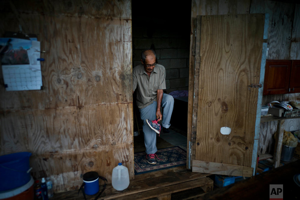 Ramon Alicea Burgos leaves the temporary room he built under his partially re-built home. Sept. 8, 2018. (AP Photo/Ramon Espinosa)