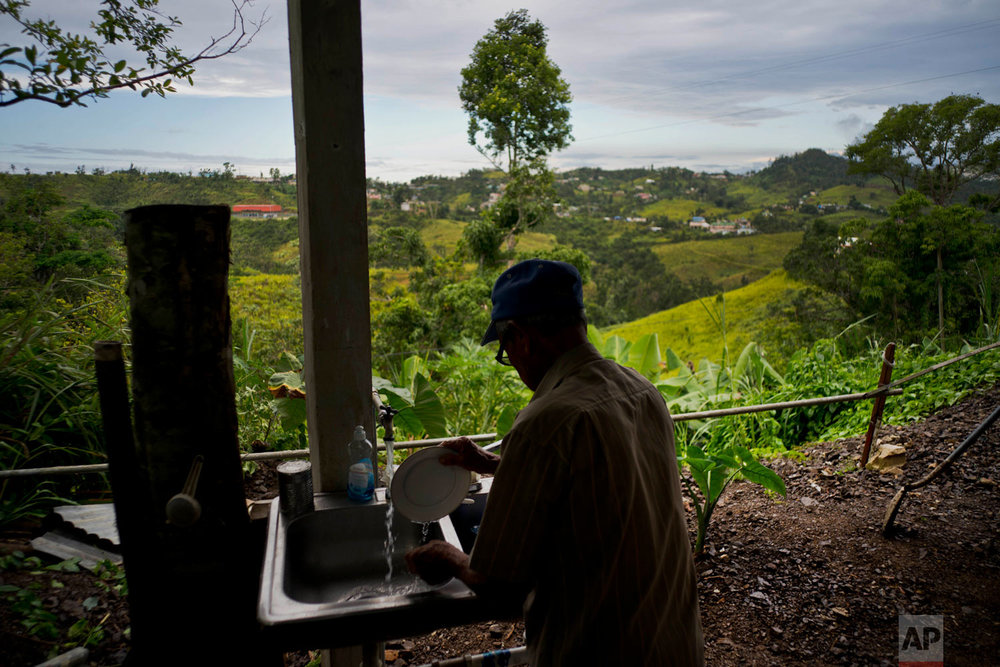 In this Sept. 8, 2018 photo, Ramon Alicea Burgos washes a plate under his partially rebuilt home, unfinished for lack of funds in the mountain town of Barranquitas, Puerto Rico. (AP Photo/Ramon Espinosa)