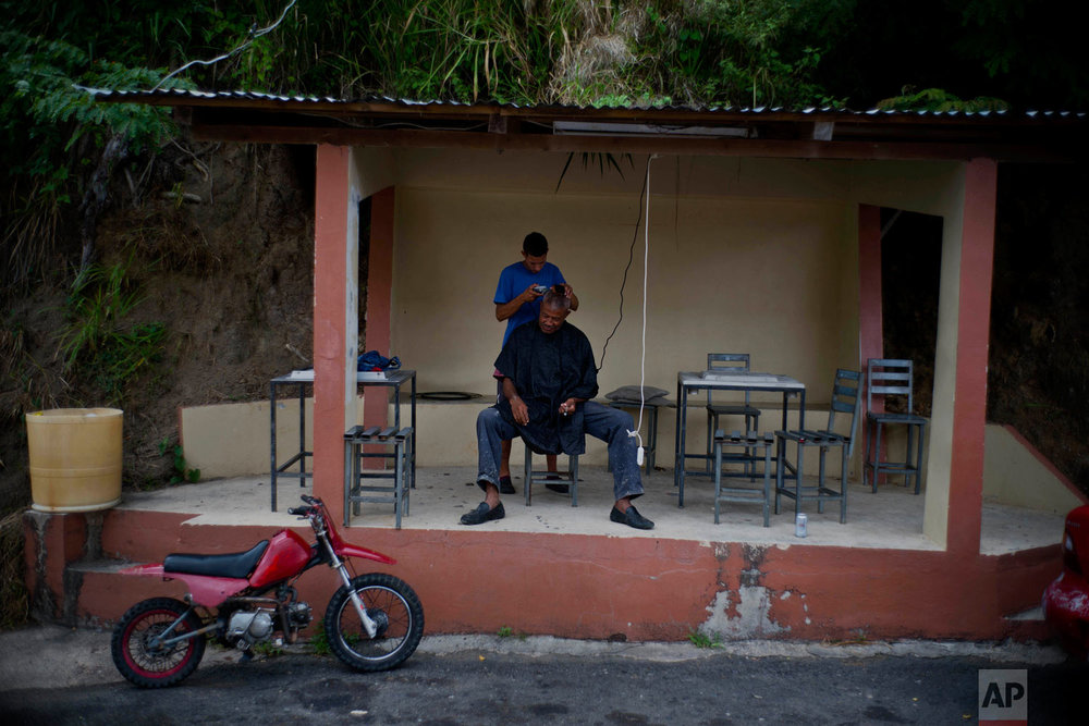 In this Sept. 8, 2018 photo, farm worker Angel Reyes gets a haircut by professional barber Luis Otero, who offers his service at a bus stop for $7 dollars, on Morovis road to Orocovis, Puerto Rico. Reyes said the storm broke his home's windows and part of the roof, but FEMA denied him rebuilding assistance, so he decided to take his government pension in one lump sum, instead of monthly payments. (AP Photo/Ramon Espinosa)