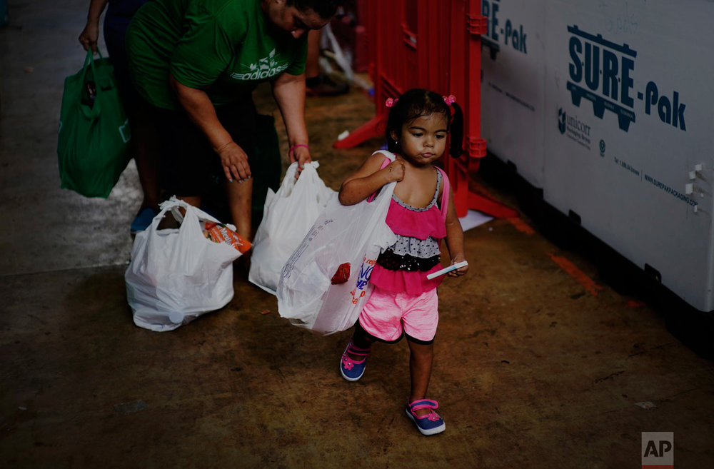 In this Sept. 13, 2018 photo, a girl helps her mother carry donated food and other staples handed out to needy residents by the MARC Ministry, a non-profit charity in Manati, Puerto Rico. (AP Photo/Ramon Espinosa)