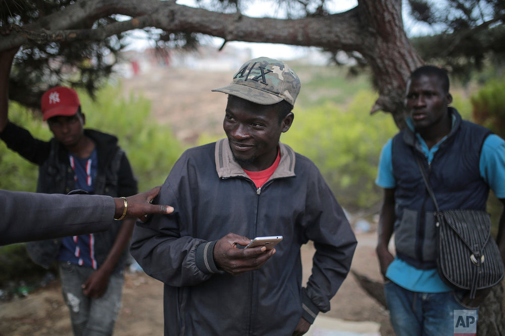 Youness Piichpa, a sub-Saharan migrant from Cameroon interacts with friends, as they take shelter in a forest overlooking the neighborhood of Masnana, Sept. 8, 2018, on the outskirts of Tangier, Morocco. (AP Photo/Mosa'ab Elshamy)