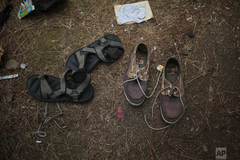 Shoes belonging to sub-Saharan migrants aiming to cross to Europe are scattered on in a forest following a police raid, Sept. 8, 2018, near Masnana, on the outskirts of Tangier, Morocco. (AP Photo/Mosa'ab Elshamy)