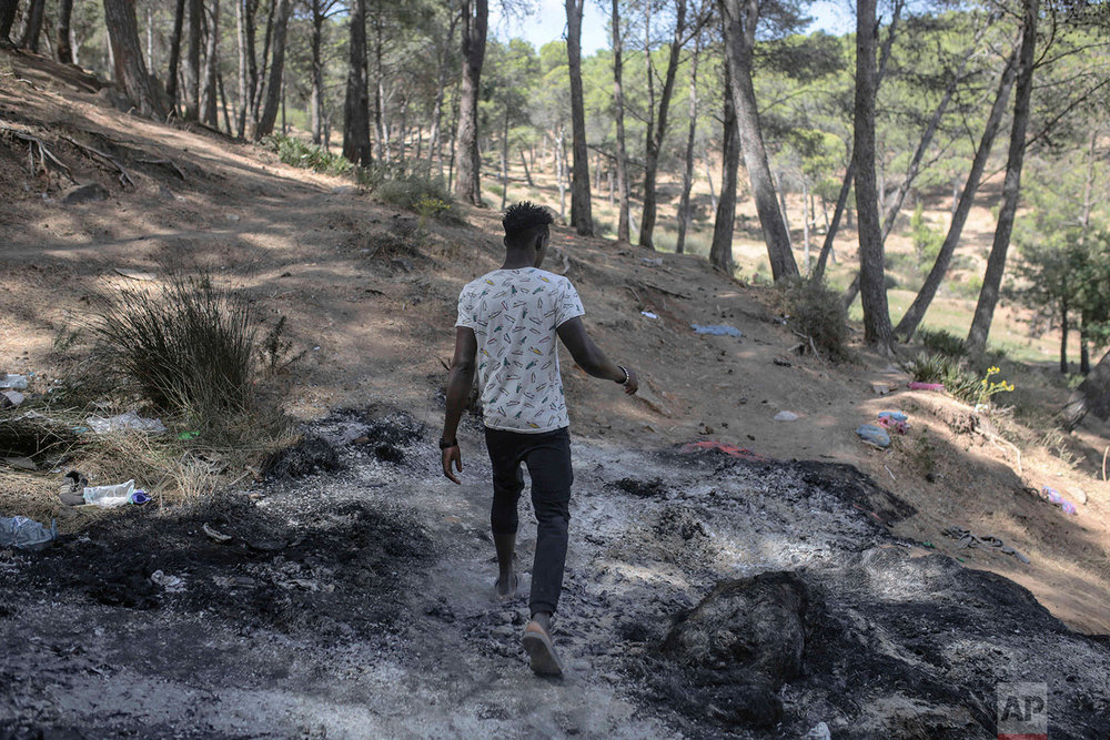 A sub-Saharan migrant aiming to cross to Europe walks on a burnt patch following a raid by police, near Masnana, Sept. 5, 2018, on the outskirts of Tangier, Morocco. (AP Photo/Mosa'ab Elshamy)