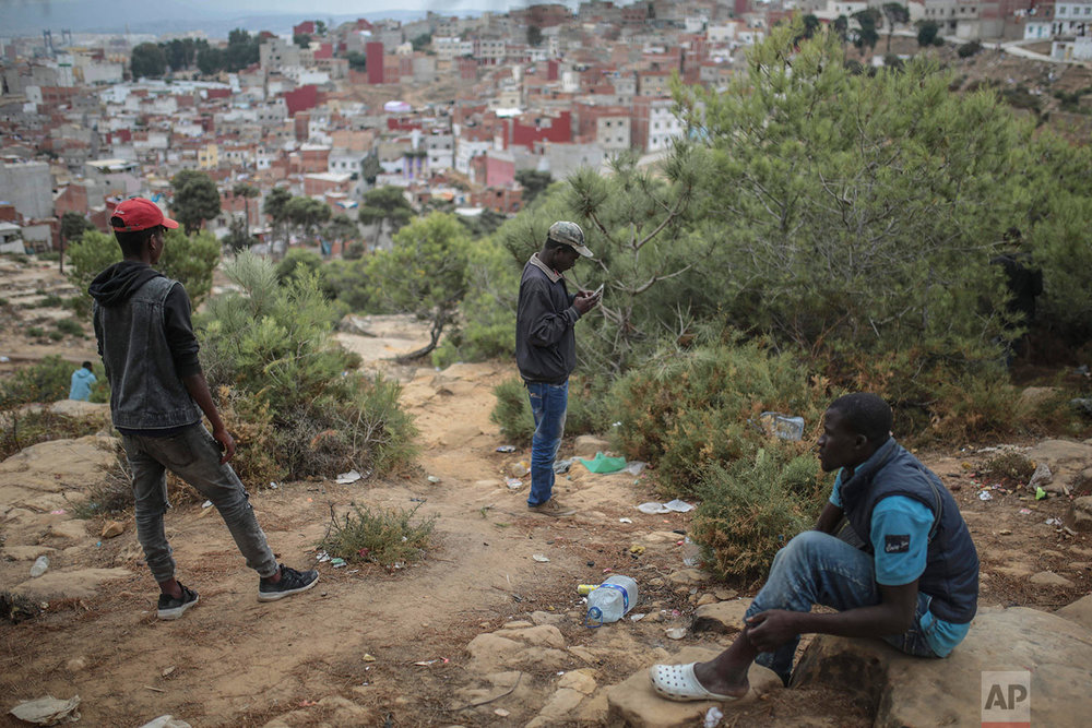 Sub-Saharan migrants aiming to cross to Europe take shelter in a forest overlooking the neighborhood of Masnana, Sept. 8, 2018, on the outskirts of Tangier, Morocco. (AP Photo/Mosa'ab Elshamy)