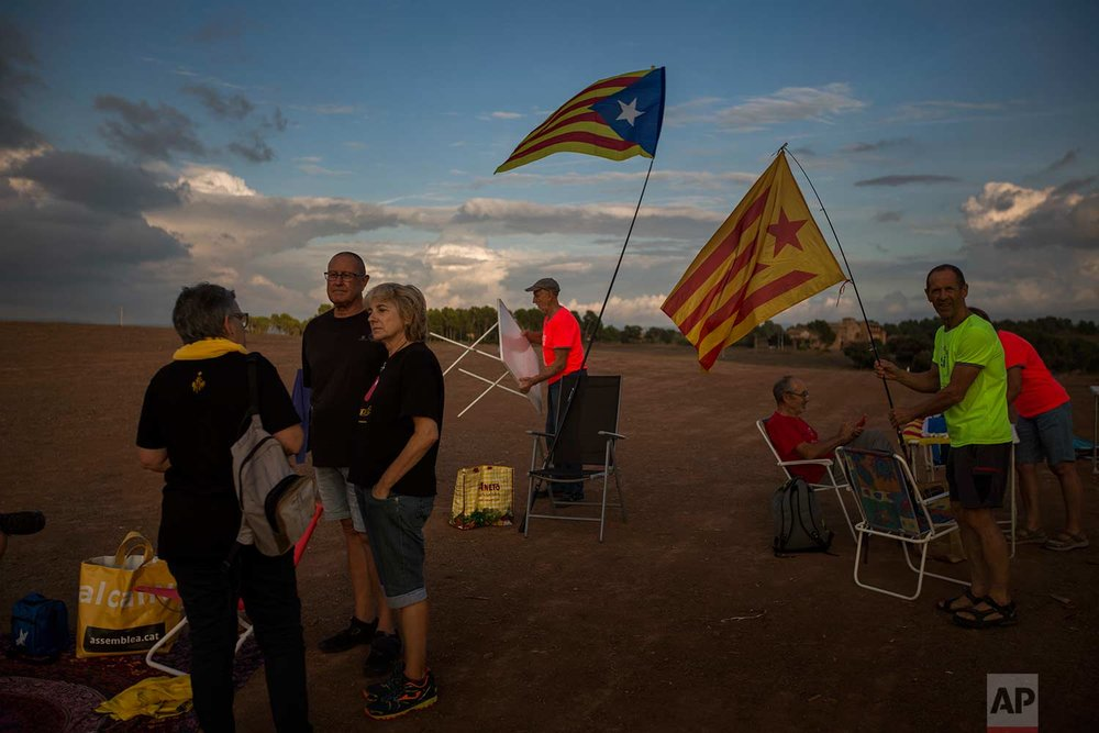 In this Tuesday, Sept. 18, 2018 photo, pro independence supporters set their chairs and tables to make a picnic on a field overlooking the Lledoners prison in Sant Joan de Vilatorrada, about 50 kilometres away from Barcelona, Spain. (AP Photo/Emilio Morenatti)