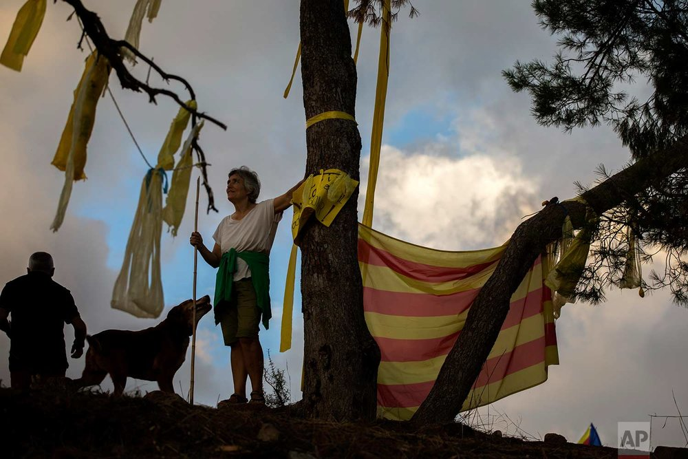 In this Tuesday, Sept. 18, 2018 photo, pro independence people arrive on a hill overlooking the Lledoners prison, in Sant Joan de Vilatorrada, about 50 kilometres away from Barcelona, Spain. (AP Photo/Emilio Morenatti)