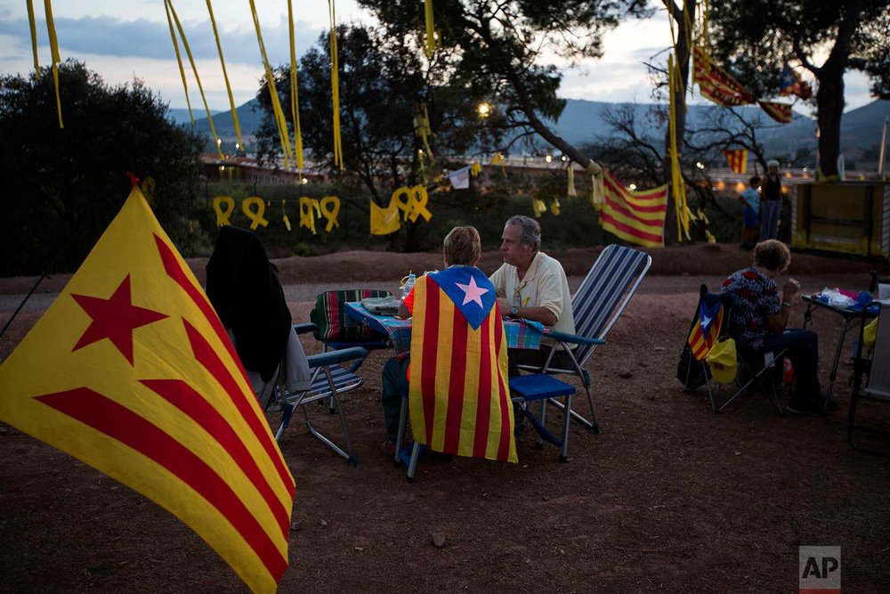 """In this Tuesday, Sept. 18, 2018 photo, pro independence people, some of them wearing """"esteladas"""" or independence flags, enjoy a picnic on a field overlooking the Lledoners prison, in Sant Joan de Vilatorrada, about 50 kilometres away from Barcelona, Spain. (AP Photo/Emilio Morenatti)"""