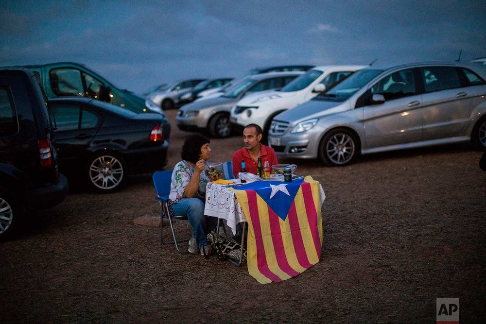 In this Tuesday, Sept. 18, 2018 photo, pro independence people enjoy a picnic on a field overlooking the Lledoners prison, in Sant Joan de Vilatorrada, about 50 kilometres away from Barcelona, Spain. (AP Photo/Emilio Morenatti)