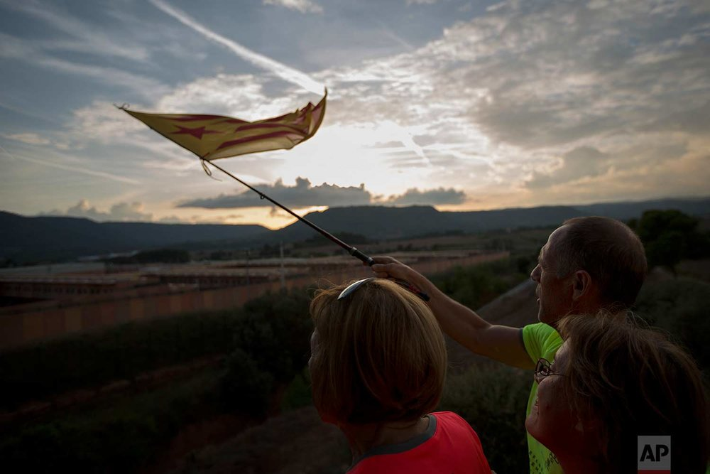"In this Tuesday, Sept. 18, 2018 photo, pro independence people, wave ""esteladas"" or independence flags on top of a hill overlooking the Lledoners prison, at the background, in Sant Joan de Vilatorrada, about 50 kilometres away from Barcelona, Spain. (AP Photo/Emilio Morenatti)"