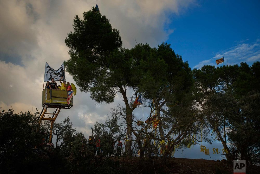 """In this Tuesday, Sept. 18, 2018 photo, a tractor lift up pro independence supporters holding a banner for former minister Jordi Turull and chanting """"freedom"""", on a field overlooking the Lledoners prison, in Sant Joan de Vilatorrada, about 50 kilometres away from Barcelona, Spain. (AP Photo/Emilio Morenatti)"""