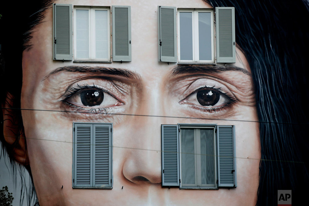 A mural depicting performance artist Marina Abramovic by Italian artist Maurizio Cattellan to publicize his upcoming exhibition The Artist is Present in Shanghai, China, is displayed on a facade of a building in Milan, Italy, Wednesday, Sept. 19, 2018. His exhibit's title plays with the one of Abramovic's work. (AP Photo/Luca Bruno)