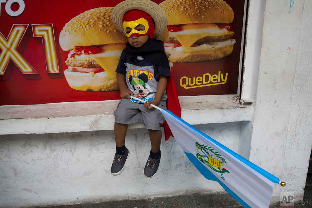 A boy wearing a costume holds a Guatemalan flag as he sits outside a local fast food restaurant waiting with his father for a march against Guatemalan President Jimmy Morales and corruption in Guatemala City, Thursday, Sept. 20, 2018. Thousands marched to protest Morales' decision to end the work of a U.N. anti-corruption commission that has helped lead high-profile graft probes targeting dozens of powerful people, including one involving Morales. (AP Photo/Moises Castillo)