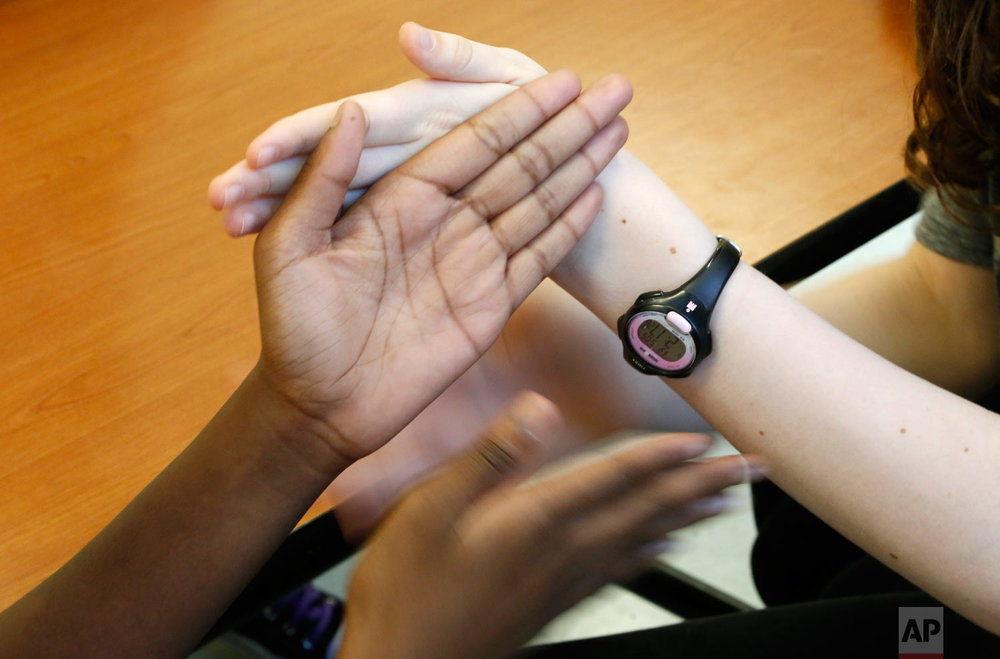 In this Friday, May 5, 2017, photo, two girls play hand-clapping games in Chicago. The students from the public Manierre Elementary School and the private Catherine Cook School came together for an art project organized by Art on Sedgwick, a neighborhood art project that aims to unite people from diverse backgrounds. (AP Photo/Martha Irvine)