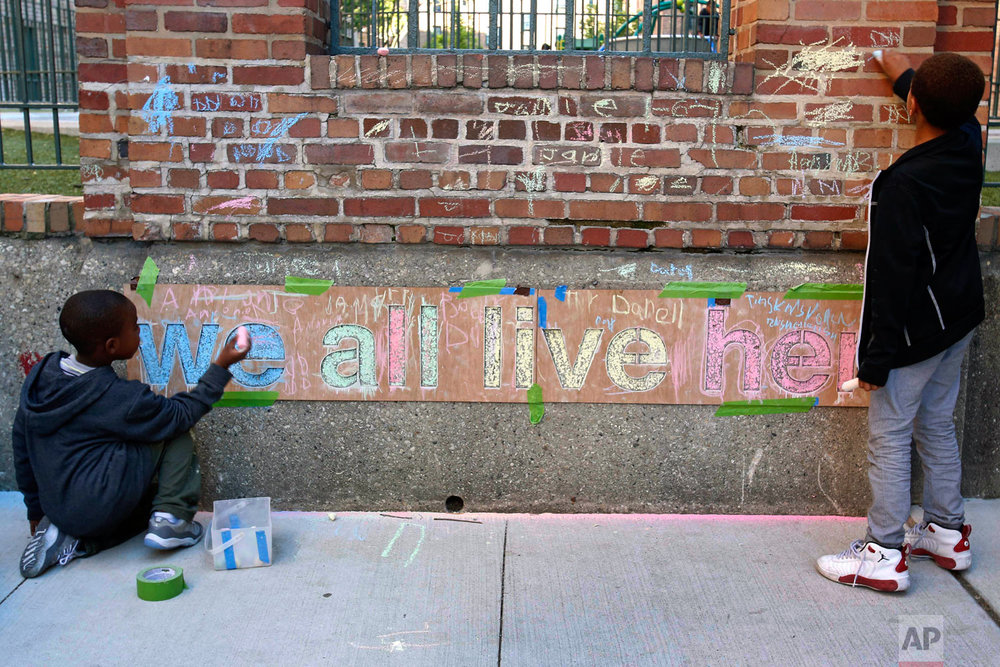 """In this June 1, 2018, photo, two boys help finish a chalk mural at Marshall Field Garden Apartments during the Art on Sedgwick annual art show in Chicago. The theme of the mural """"We all live here"""" was conceived by artist Rich Alapack who has focused the public art project at schools and community centers. (AP Photo/Martha Irvine)"""