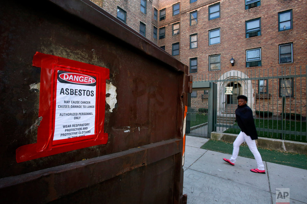 In this Oct. 18, 2015, photo, a young man walks past Marshall Field Garden Apartments in Chicago. Marshall Field Garden Apartments was purchased and renovated, beginning that same year. (AP Photo/Martha Irvine)