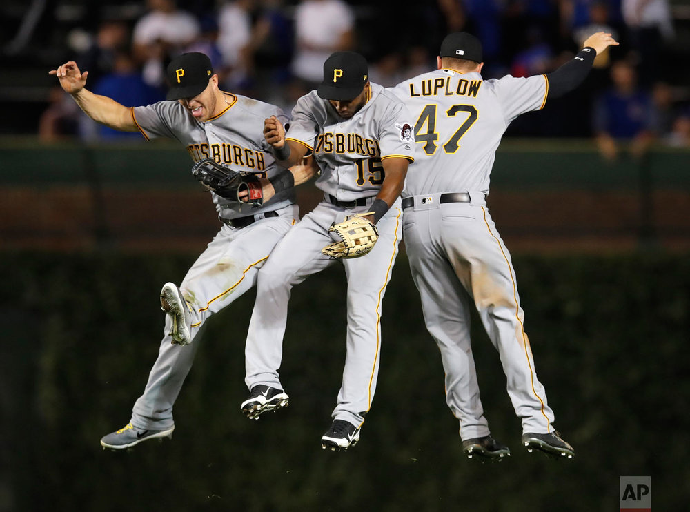 Pittsburgh Pirates' Corey Dickerson, left, Pablo Reyes, center, and Jordan Luplow celebrate their team's win against the Chicago Cubs at the end of a baseball game Monday, Sept. 24, 2018, in Chicago. (AP Photo/Jim Young)