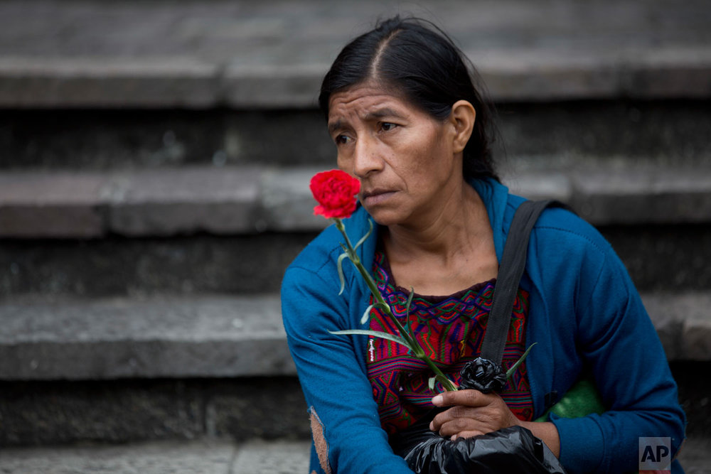 An Ixil indigenous woman holds a red carnation during a memorial for the victims of the civil war, after the former director of military intelligence Jose Rodriguez Sanchez, delivered his statement at a courtroom in Guatemala City, Wednesday, Sept. 26, 2018. Judges unanimously held that genocide and crimes against humanity were committed by the military, but disagreed on whether it was proven that Rodriguez gave the commands. (AP Photo/Moises Castillo)