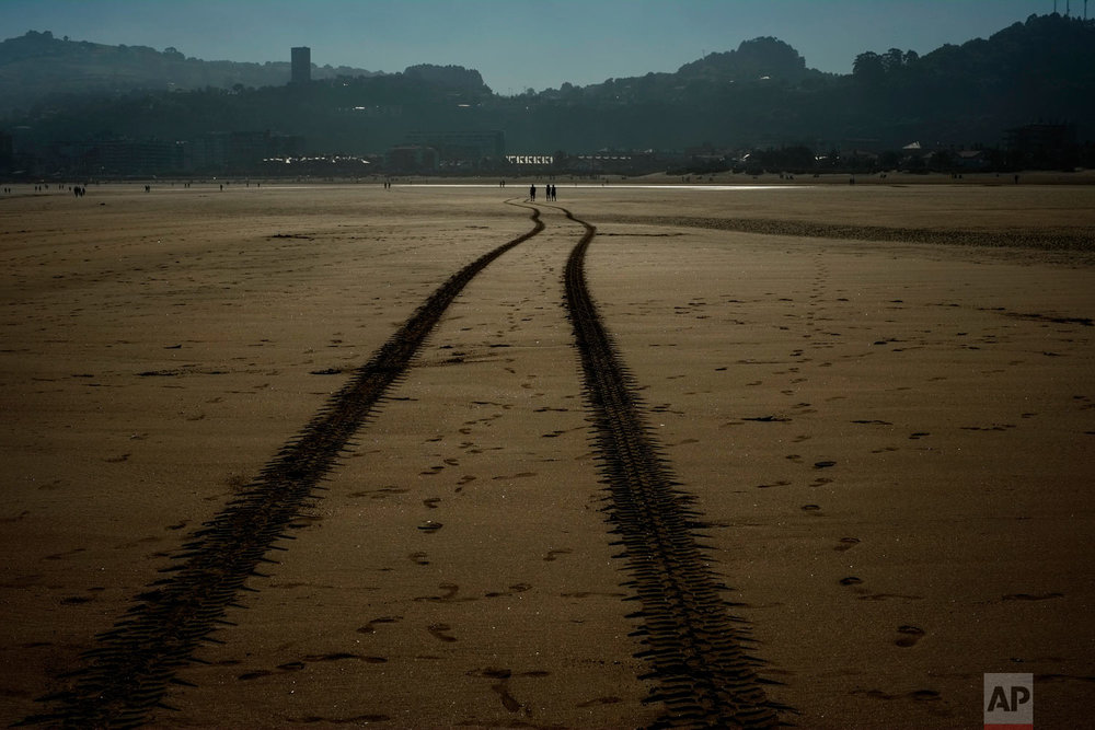 People walk across the beach next to the marks of a tractor during an autumn morning in Laredo, northern Spain, Sunday, Sept. 23, 2018. (AP Photo/Alvaro Barrientos)