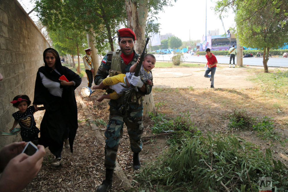 In this provided by Mehr News Agency, an Iranian soldier carries a child away from a shooting during a military parade, in the southwestern city of Ahvaz, Iran on Sept. 22, 2018. (AP Photo/Mehr News Agency, Mehdi Pedramkhoo)