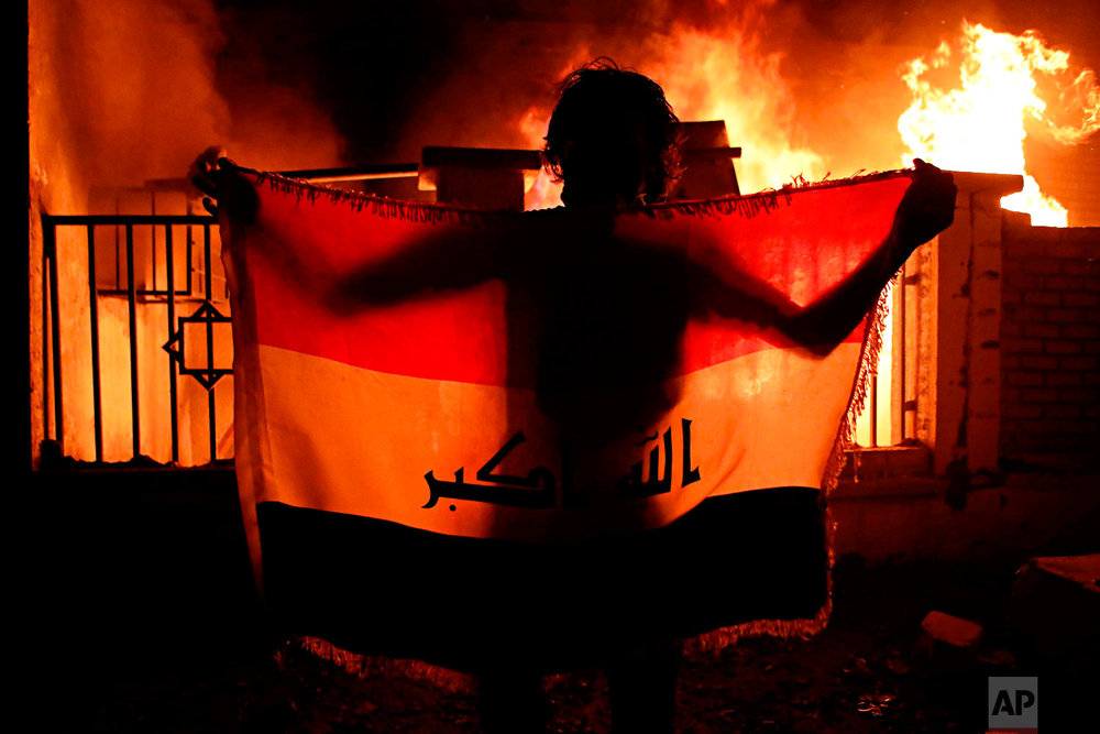 A man holds a national flag while protesters burn the municipal complex during protests demanding better public services and jobs in Basra, 340 miles (550 km) southeast of Baghdad, Iraq, Sept. 5, 2018. (AP Photo/Nabil al-Jurani)