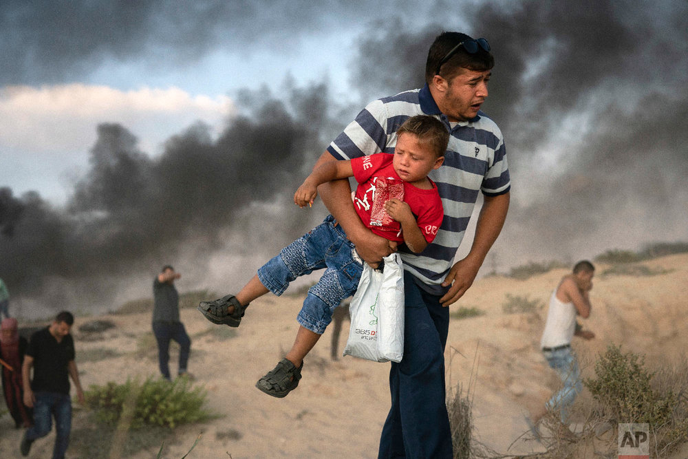 A Palestinian protester carries a boy as he runs from tear gas fired by Israeli soldiers during a protest on the beach near the border with Israel in Beit Lahiya, northern Gaza Strip, Monday, Sept. 10, 2018. (AP Photo/Felipe Dana)