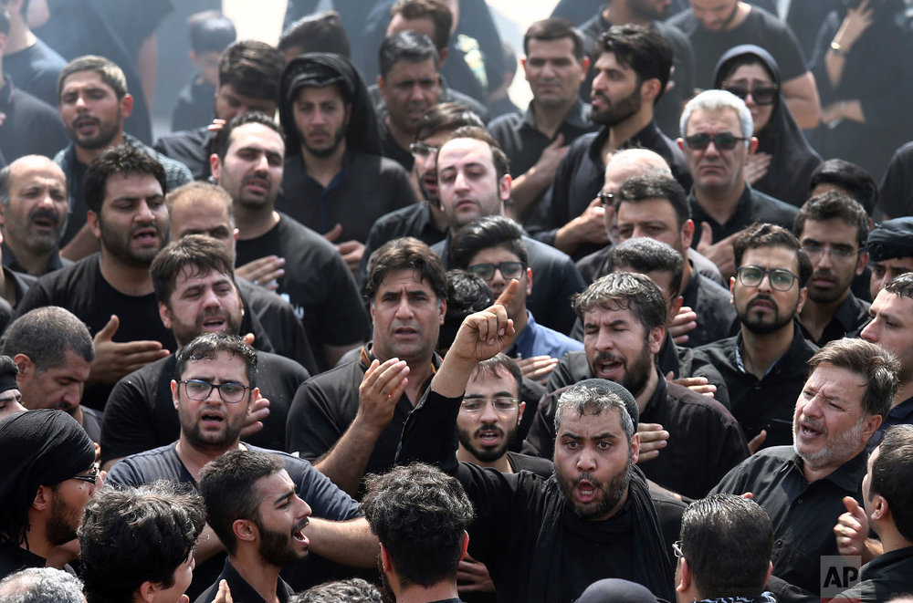 Iranian and Iraqi Shiite men mourn during the holy day of Ashoura, in southern Tehran, Iran, Sept 20, 2018. (AP Photo/Ebrahim Noroozi)