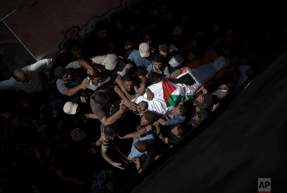 Mourners carry the body of Palestinian Muhammed al-Sadiq, 21, into the family home during his funeral in Gaza City, Sept. 25, 2018. (AP Photo/Khalil Hamra)
