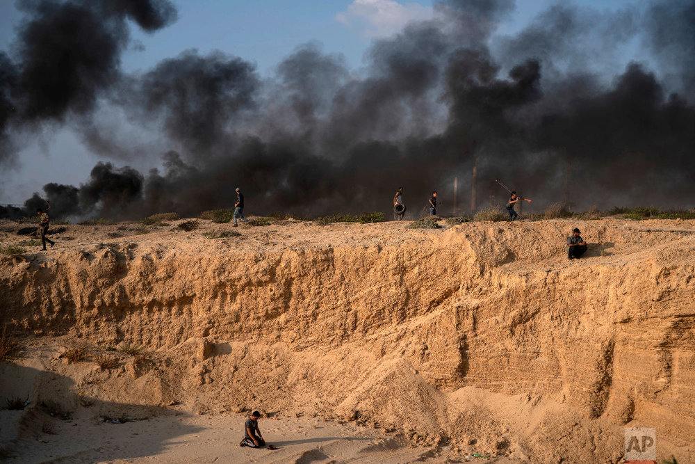 A Palestinian protester prays as others hurl stones and burn tires during a protest on the beach near the border with Israel in Beit Lahiya, northern Gaza Strip, Sept. 10, 2018. (AP Photo/Felipe Dana)