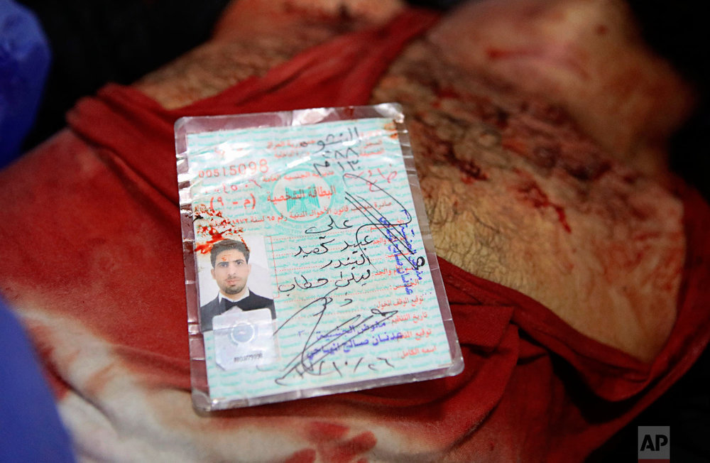 The blood-stained identification card of Ali Obaid, killed during a protest, lies on his body, Tuesday, Sept. 4, 2018, in Basra, 340 miles (550 kilometers) southeast of Baghdad, Iraq.(AP Photo/Nabil al-Jurani)