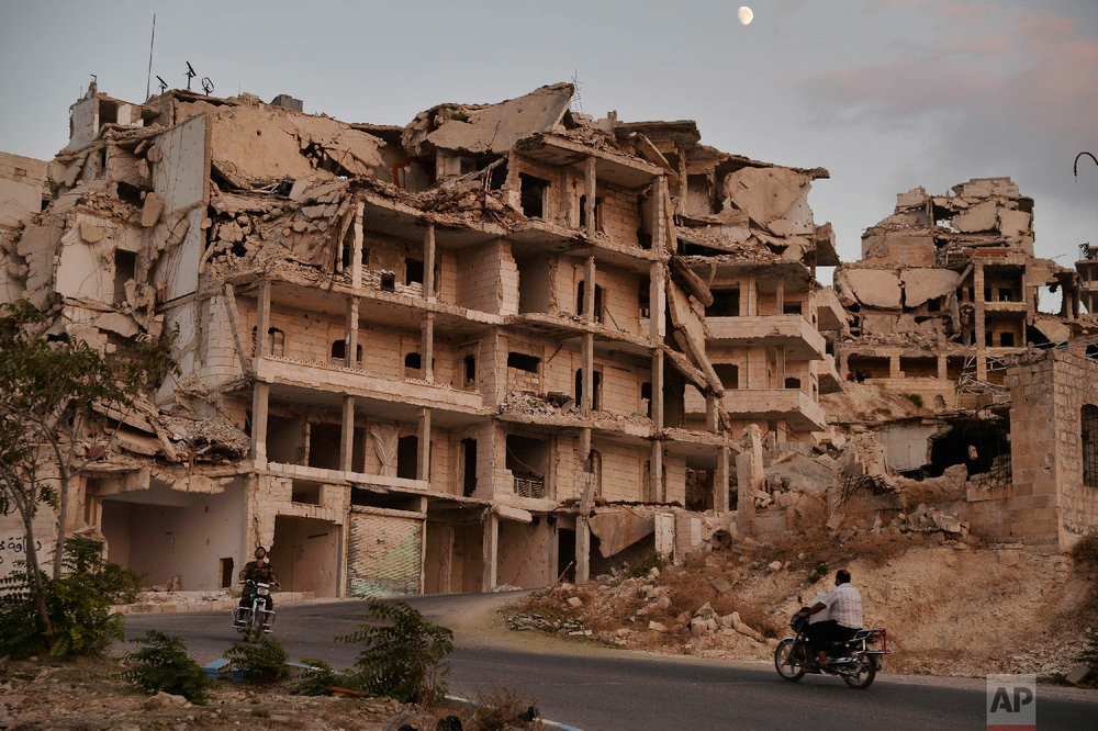 Motorcycles ride past buildings destroyed during the fighting in the northern town of Ariha, in Idlib province, Syria on Sept. 20, 2018. (Ugur Can/DHA via AP)