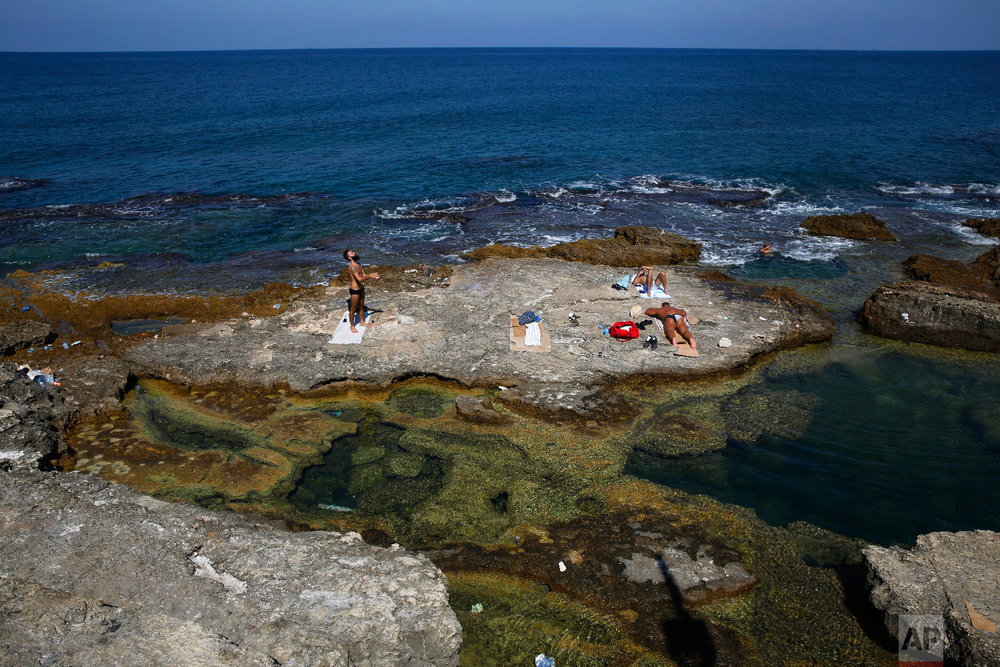 Lebanese men sunbathe on the rocky shore of the Mediterranean Sea off the Corniche, or waterfront promenade, in Beirut, Lebanon, Sept. 26, 2018. (AP Photo/Hussein Malla)