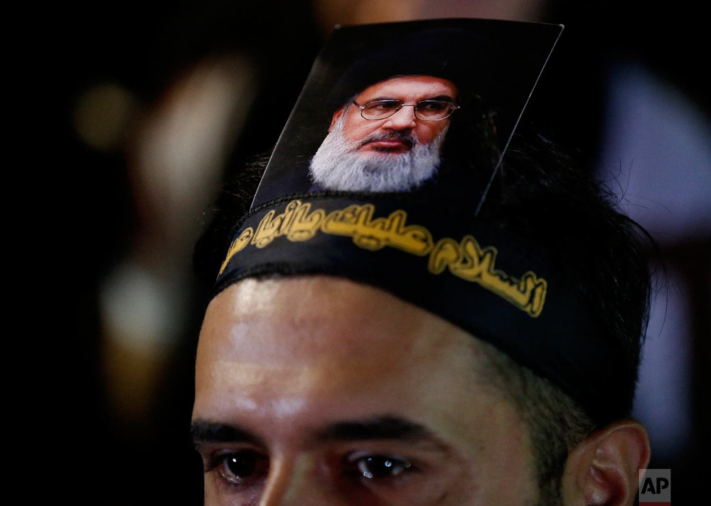 A Lebanese Shiite supporter of the Iranian-backed Hezbollah group, with a portrait on his head of Hezbollah leader Sheikh Hassan Nasrallah, attends an activities to mark the ninth of Ashura, a 10-day ritual commemorating the death of Imam Hussein, in a southern suburb of Beirut, Lebanon, Sept. 19, 2018. (AP Photo/Hussein Malla)