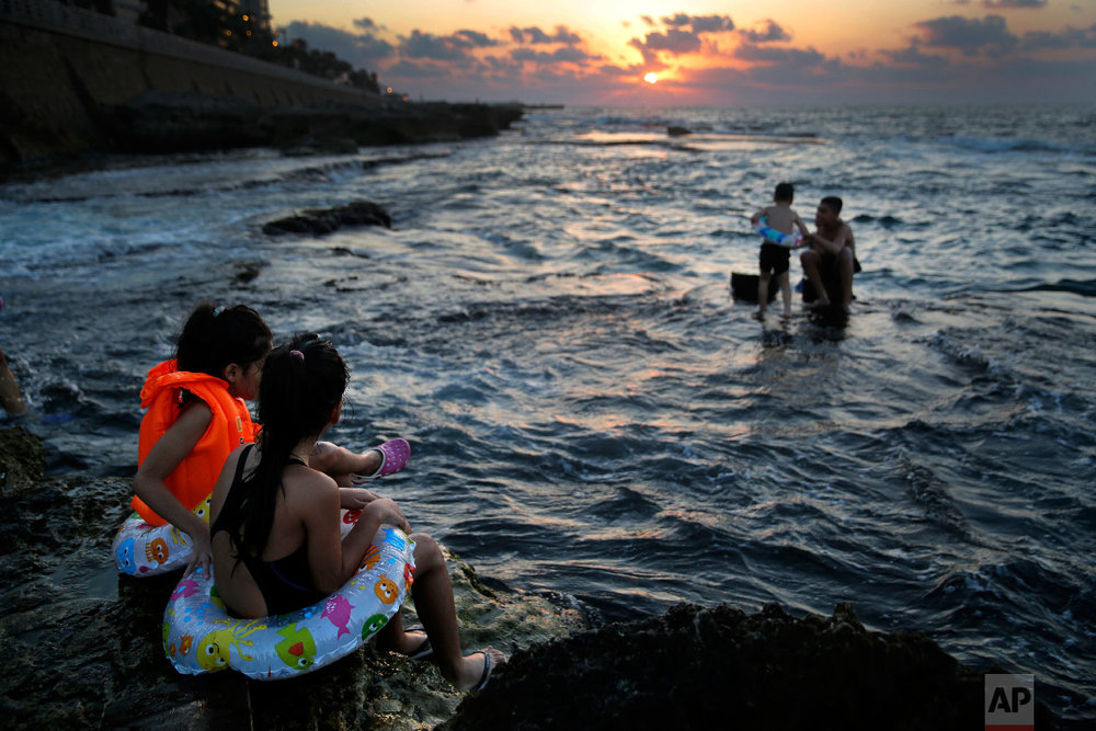Lebanese young girls sit on a rock and enjoy the Mediterranean Sea off the Corniche, or waterfront promenade, as the sunset during the last day of summer season, in Beirut, Lebanon, Sept. 20, 2018. (AP Photo/Hussein Malla)