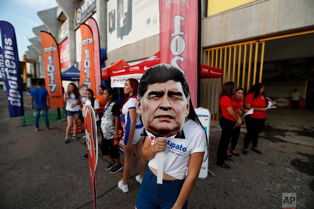 An event promoter holds a mask of former soccer star Diego Maradona, head coach of Dorados de Sinaloa soccer team, at the venue of a second-tier national league soccer match against Cafetaleros, his first game as coach for Dorados in Culiacan, Mexico, Sept. 17, 2018. (AP Photo/Eduardo Verdugo)