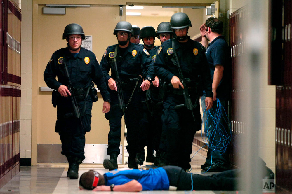"""In this May 29, 2008 photo, Baton Rouge Police Department SWAT team members walk down a McKinley Middle Magnet School hallway past a fire academy member playing the role of a victim during a simulated hostage situation in Baton Rouge, La. High-tech hardware installed by NetTalon Security Systems reduced """"casualties"""" during the exercise, according to then-principal Herman Brister. But in hindsight, he said he would have rather hired an armed resource officer. (Richard Alan Hannon/The Advocate via AP)"""