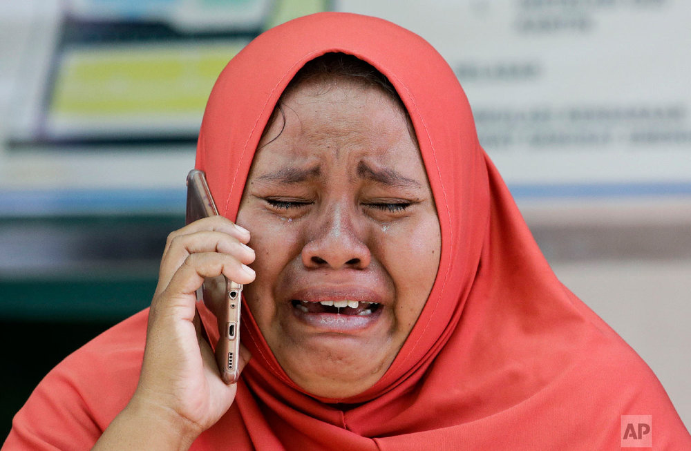 A woman cries as she uses the recovered mobile phone of her daughter who was killed in the earthquake at Palu, Central Sulawesi, Indonesia on Oct. 4, 2018. (AP Photo/Aaron Favila)