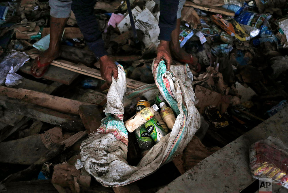 A man put beverages he scavenged from an abandoned warehouse into a sack at an earthquake and tsunami-affected area in Palu, Central Sulawesi, Indonesia Indonesia, Oct. 3, 2018. (AP Photo/Dita Alangkara)