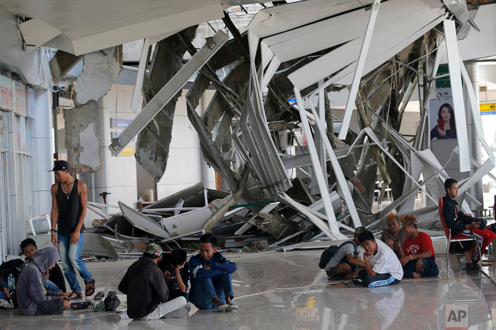 People sit outside Mutiara Sis Al-Jufri airport damaged by a powerful earthquake and tsunami in Palu, Central Sulawesi Indonesia, Oct. 4, 2018. (AP Photo/Tatan Syuflana)