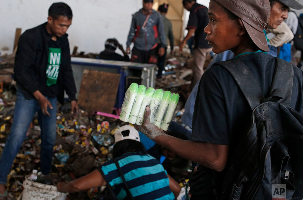 A man holds bottles of body lotions he scavenged from an abandoned warehouse at an earthquake and tsunami-affected area in Palu, Central Sulawesi, Indonesia Indonesia, Oct. 3, 2018. (AP Photo/Dita Alangkara)