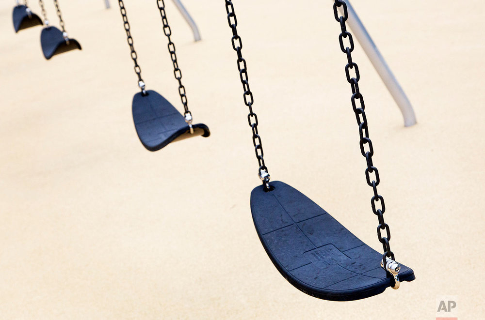 Empty playground swings are in place at the new Sandy Hook Elementary School, July 29, 2016, in Newtown, Conn. (AP Photo/Mark Lennihan)