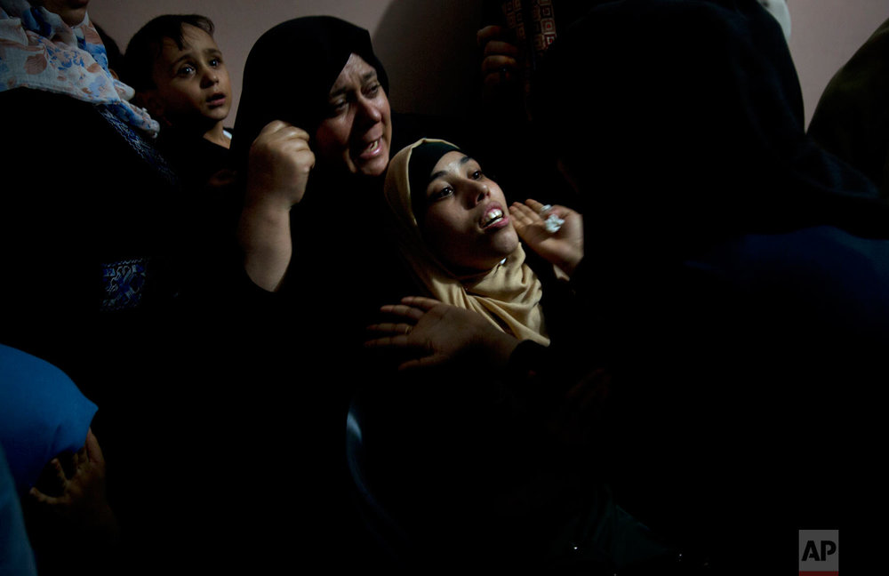 Palestinian relatives of 14 year-old Mohammed al-Houm, who was shot and killed by Israeli troops on Friday's ongoing protest at the Gaza Strip's border with Israel, mourn at the family's home during his funeral in Bureij refugee camp, central Gaza Strip, Saturday, Sept. 29, 2018. (AP Photo/Khalil Hamra)