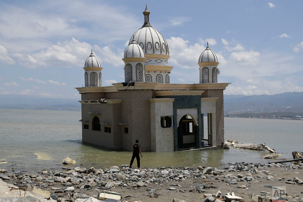 A man looks at a mosque that was isolated by water after its bridge was destroyed due to the massive earthquake and tsunami in Palu, Central Sulawesi, Indonesia Friday, Oct. 5, 2018. More than 1,500 people were killed in the area. (AP Photo/Aaron Favila)
